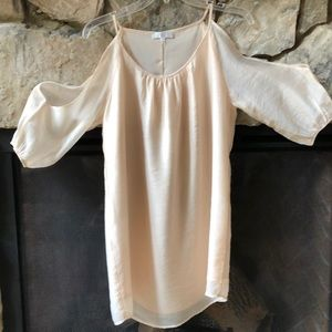 Cream dress with 3/4 sleeves open on shoulder.